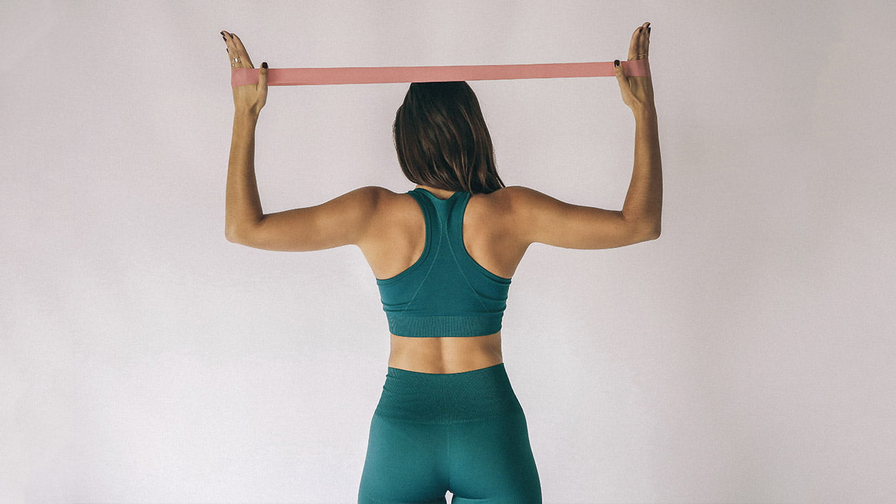 woman exercising with Muki resistance band