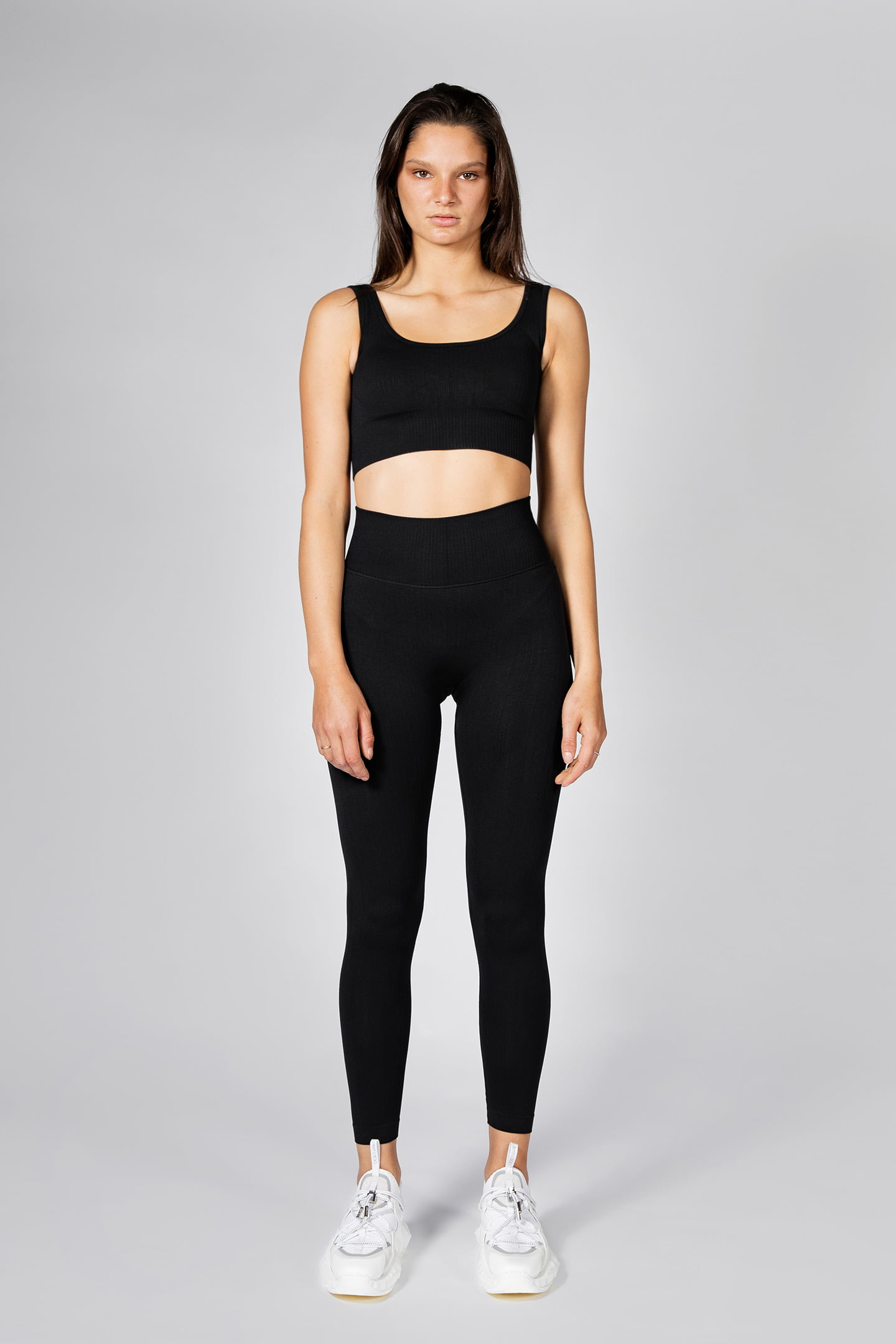 model posing in seamless ribbed workout leggings and seamless sports bra in black colour