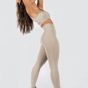 woman posing in yoga pants and seamless sports bra in beige colour