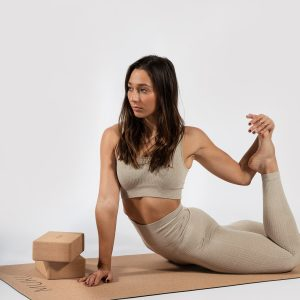 woman stretching in women's sports bra on cork yoga mat by Muki
