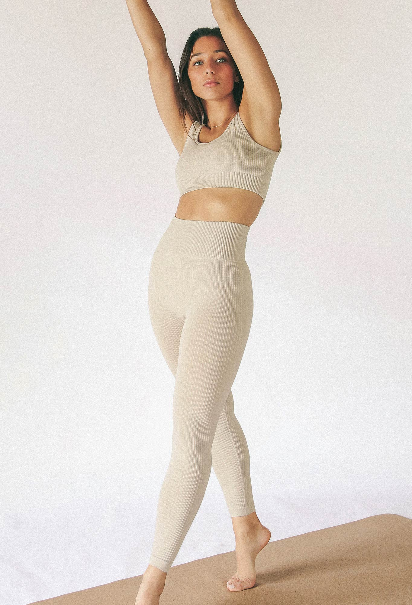 model wearing seamless sports bra and seamless legging in beige colour