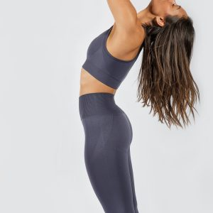 woman stretching in Muki sports bra and yoga pants in grey colour