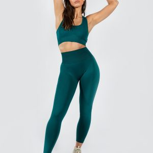 model posing in women's yoga pants and seamless sports brea in emerald green