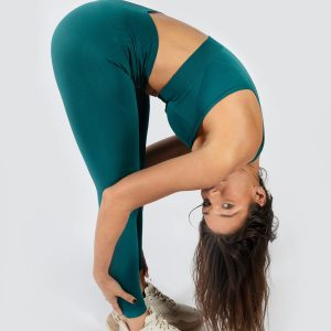 woman stretching in Muki seamless yoga set in emerald green colour