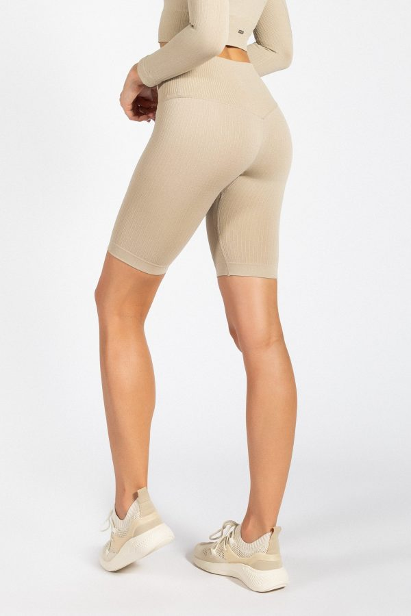 model wearing high-waisted ribbed biker short in cream colour